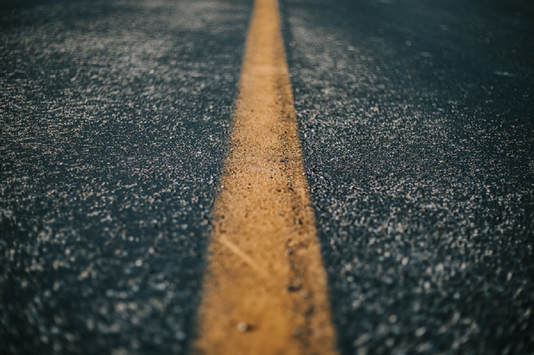 Close up of a yellow line painted on the road