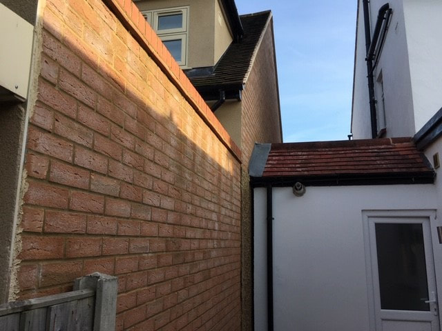 Image of a neighbours extension up to the boundary wall. Antino and Associates can assess this under the Party Wall Act.